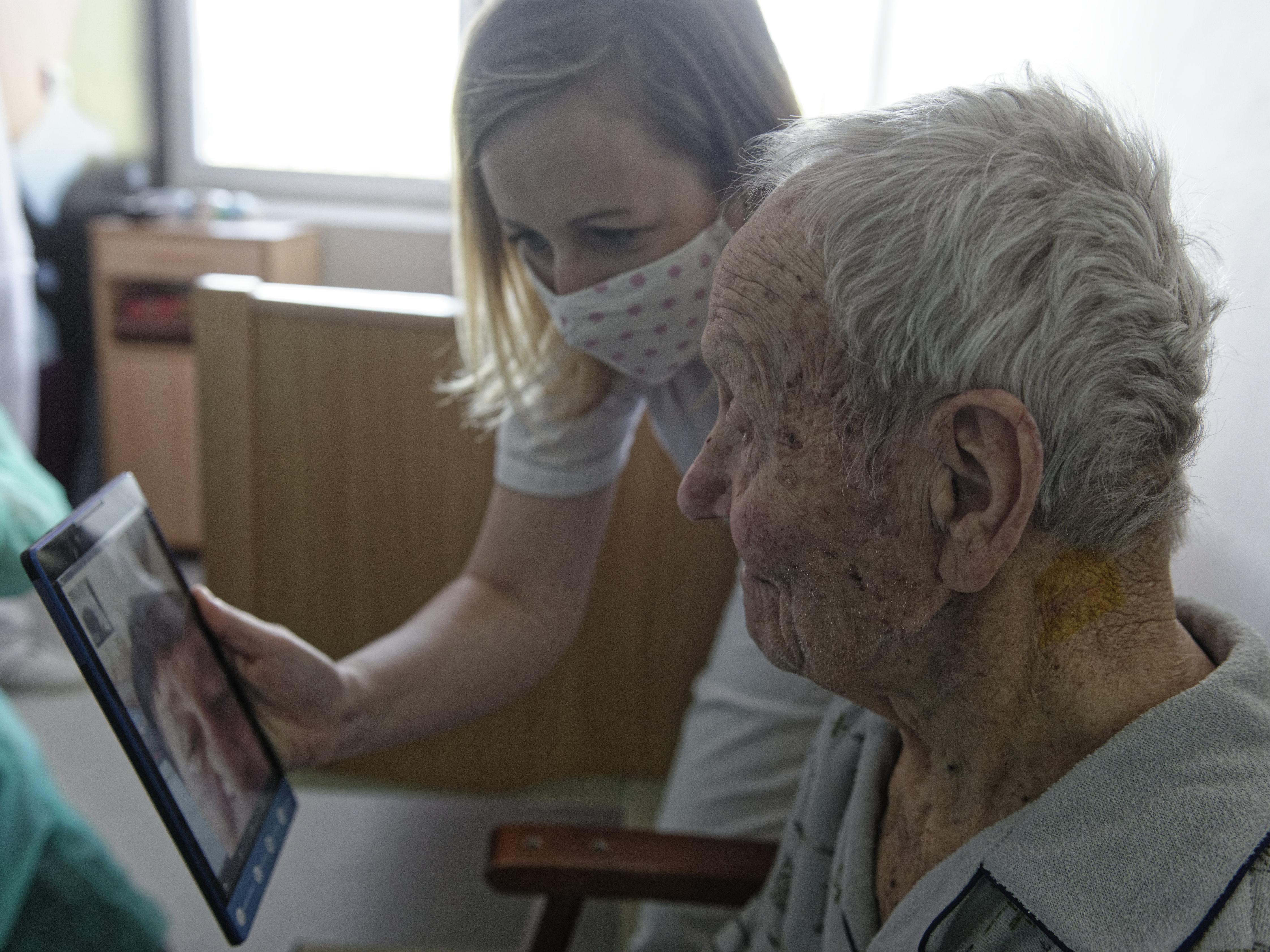Sestrička im donesie tablet a nastaví videohovor s rodinou
